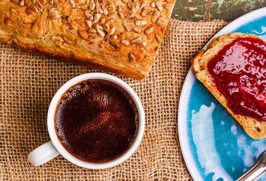 Chleb wlasnej roboty na sniadanie. Goraca kawa. Pozywne sniadanie przed praca. Kawa i kanapki na niebieskim talerzu. Zdjecie z gory.