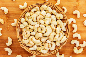 Healthy cashew nuts stuffed in wicker bowl on wooden background. Top view. Food photography. Healthy fresh cashew nuts. Minimalist photography. The Latin name of cashew is Anacardium occidentale.