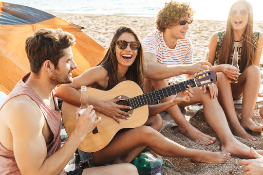 Group of cheerful happy friends camping at the beach