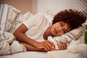 Millennial African American woman lying ill in bed looking to camera, close up