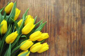 A bouquet of yellow tulips in a vase on the floor. A gift to a woman's day from yellow tulip...