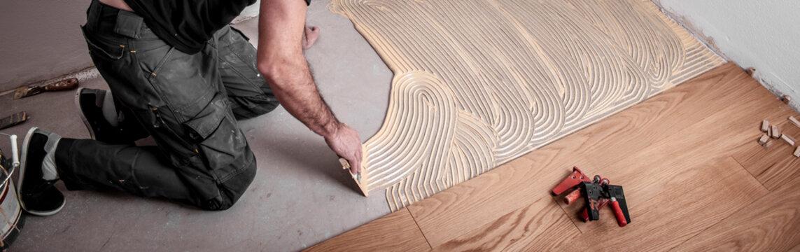 Handwerker verlegt Parkettboden und streicht den Estrich mit Kleber ein und schlägt die Dielen mit dem Hammer und dem Schlagklotz zusammen
