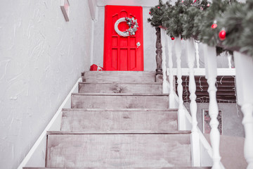 Decorated with New Year's decor, a staircase leads to the second floor to the red door.