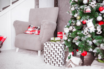 a large easy chair with a plaid and Christmas gifts under the tree
