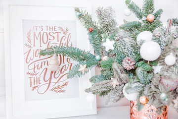 picture with Christmas inscription stands next to a vase and Christmas tree branches