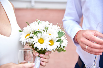 Bride and groom hold glasses of champagne and a bouquet on their wedding day