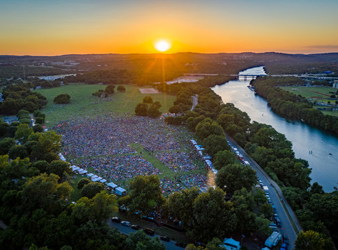 Image of large crowd attending an Outdoor Concert at Zilker Park in Austin Texas at sunset along the colorado river | aerial