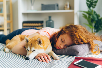 Pretty teenage girl is sleeping at home hugging adorable shiba inu dog in sleep lying on couch in apartment. Lifestyle, relaxation and animals concept.