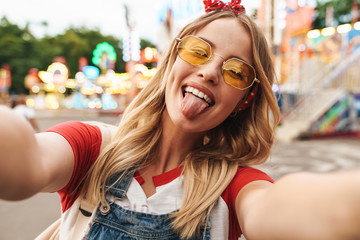 Foto op Aluminium Amusementspark Image of happy blonde woman sticking out her tongue and taking selfie photo at amusement park