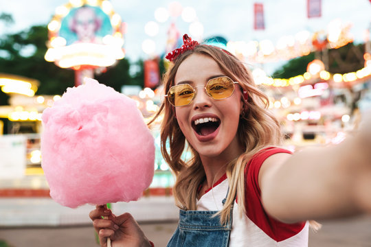 Image of excited blonde woman holding sweet cotton candy while taking selfie photo at amusement park