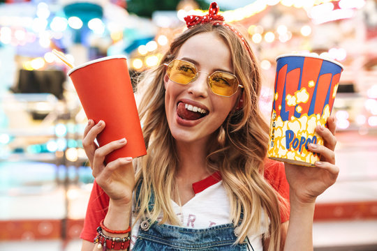 Image of happy charming woman holding popcorn and soda paper cup while walking in amusement park