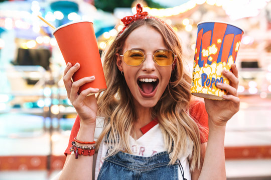 Image of joyful charming woman holding popcorn and soda paper cup while walking in amusement park