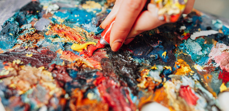 Closeup of colorful palette. Cropped shot of lefthanded female artist mixing acrylic paint.