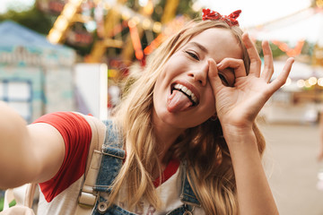 Image of happy blonde woman showing ok sign and taking selfie photo at amusement park