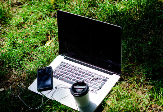 agile business. Online study. working place outdoor. Free music. summer vibes. Relax. notebook with headset of mobile phone and coffee to go on green grass. university students life. Online shopping