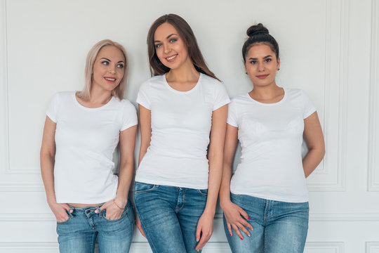 Three young smiling girls in white t-shirts and jeans on white background. T-shirt design. Mockup