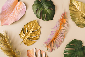 Creative layout made of colorful and golden tropical leaves and palms. Minimal summer exotic...