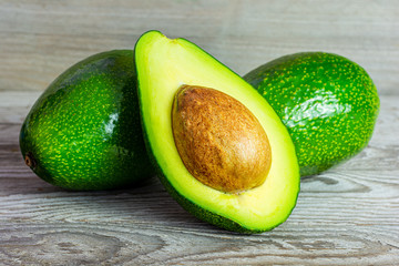 Green avocado with stone cut in two halves. A juicy green avocado on a wooden kitchen table. Healthy tropical fruits.