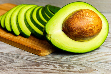 Slices of green avocado on a wooden cutting board. A juicy green avocado on a wooden kitchen table. Healthy tropical fruits.
