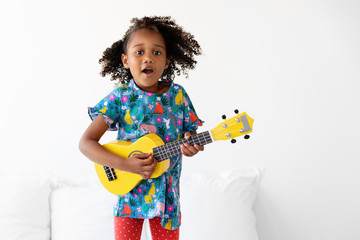 Portrait of young girl dancing on bed while playing the guitar