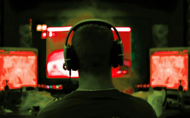 Shot of the Beautiful Pro Gamer Girl Playing in First-Person Shooter Online Video Game on Her Personal Computer. Casual Cute Geek wearing Glasses and Headset. Neon Room. eSport Cyber Games Internet