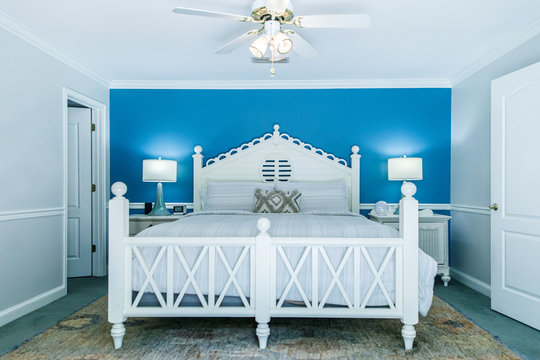 Blue and White Modern Bedroom with King Sized White Wood bed and accent table lamps