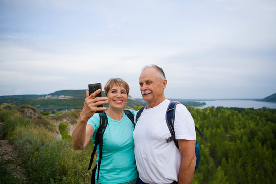 Senior couple with backpacks on the mountain taking a selfie.  Senior couple walking in nature. travel tourism concept