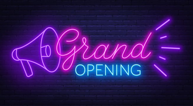 Grand opening neon sign on dark background.