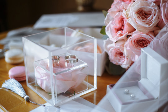 Wedding accessories on the dressing table: a bridal bouquet of pink roses, wedding rings in a transparent box, earrings in a box, a bottle of perfume, veil, invitations, macarons