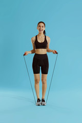 Sport woman with fit body in sportswear and skipping rope