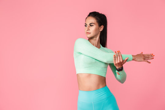 Sports fitness woman isolated over pink wall background make stretching exercises.