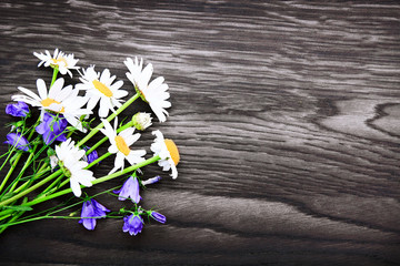 Bouquet of blue flowers and white daisies on gray wood background.