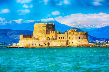 Bourtzi fortress in the sea in Nafplio or Nafplion and snow mountain peaks in Greece, Peloponnese Fototapete