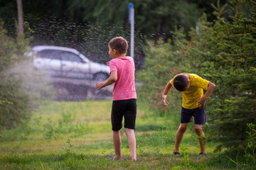 Funny boys playing with a garden sprinkler in a sunny courtyard. Preschooler kid having fun with splashing water. Summer outdoor recreation for children