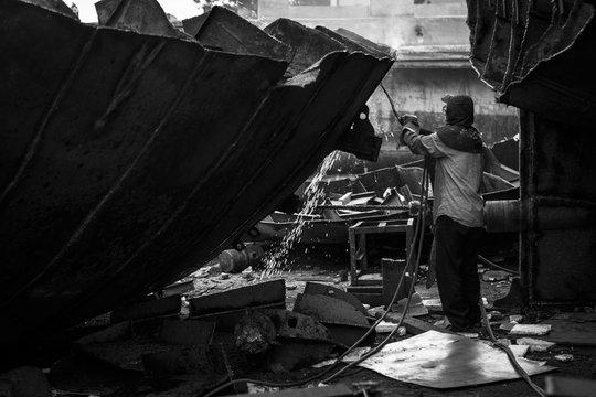 Zhuhai/China – April, 23rd 2017: Shipbreaking Yard in Zhuhai, worker dismantling with scrap metal, using gas to cut barge, ship