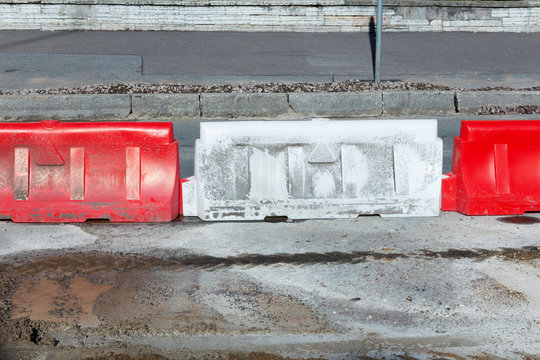 White and red mobile plastic water pressure barriers for temporary restriction of the working area without access. Road barriers at the construction site when repairing streets