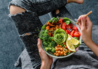 Fototapeta Woman in jeans holding Buddha bowl with salad, baked sweet potatoes, chickpeas, broccoli, greens, avocado, sprouts in hands. Healthy vegan food, clean eating, dieting, top view obraz