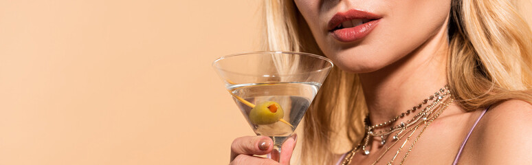 cropped view of elegant blonde woman in necklace holding cocktail isolated on beige, panoramic shot Wall mural