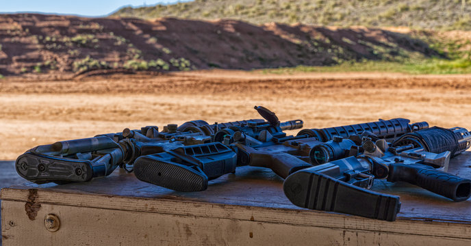 AR15 style carbine rifles staged on bench at outdoor range