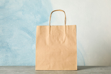 Paper bag on grey table against blue background, copy space