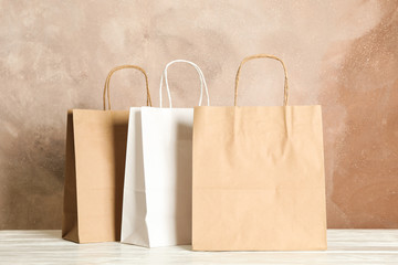 Paper bags on white table against brown background, copy space