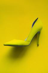 Photo of trendy fancy modern fashionable women luxury yellow high heel shoe on a yellow background in studio