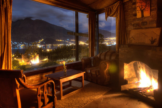 Interior of a cozy cabin at night, with a lit fireplace and a beautiful view of the San Pablo lake and Imbabura volcano, Ecuador.