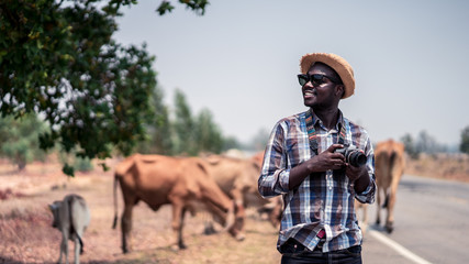 African man photographer traveling in countryside with cows.16:9 style.