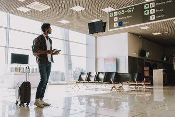 Wall Mural - Young man is waiting for plane in lounge