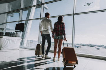 Loving couple is waiting for flight at airport Wall mural