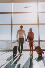 Wall Mural - Loving couple is looking at plane from lounge