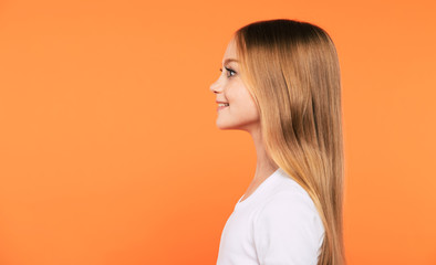 Side view portrait of beautiful little blonde girl in white t-shirt is posing isolated on yellow background Wall mural