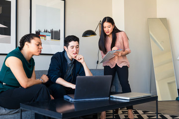 Business team looking at laptop in office