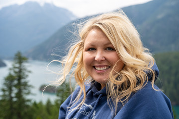 Blonde woman bundled up in a cozy hooded sweatshirt at the Diablo Lake in North Cascades National Park in Washington State. Hair blowing in wind